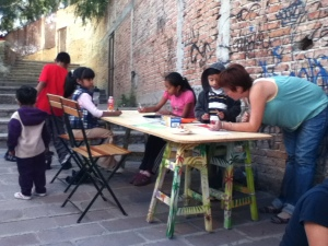 Katie Clancy making art with children at 11/2012 callejón fiesta.